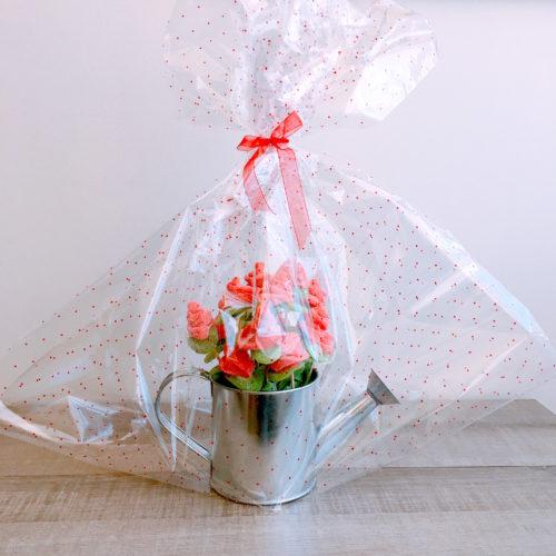 Regadera con rosas envuelta en papel